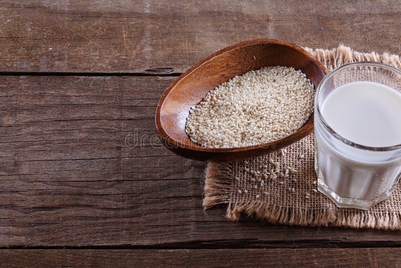 Lait de la graine de sésame au-dessus de fond en bois rustique photo stock