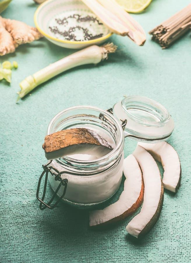 Lait de noix de coco dans le pot en verre avec des tranches de noix de coco pour la cuisson savoureuse sur le fond de turquoise D photo stock
