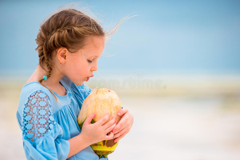 Lait de noix de coco potable de petite fille adorable sur la plage photo stock