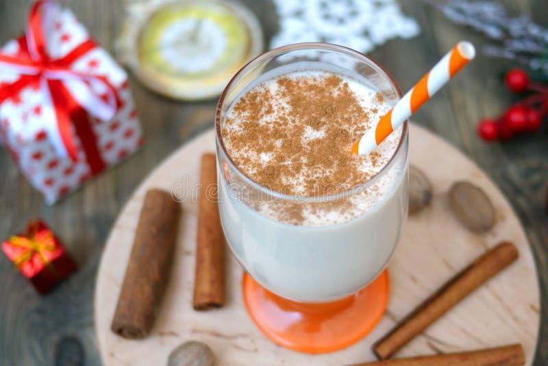 Lait de poule chaud épicé de boissons de Noël traditionnel fait maison avec la noix de muscade moulue, cannelle dans un verre, po image stock