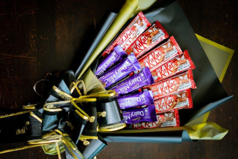 Lait et Kit Kat de laiterie de Cadbury, bonbons au chocolat et fleurs dans le bouquet doux comme cadeau pour la célébrité image libre de droits