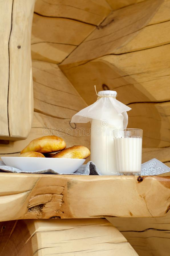 Lait frais dans une bouteille en verre et un verre, ? c?t? des tartes sur une table en bois Le concept des produits biologiques s photos stock