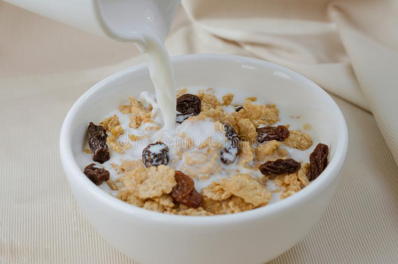Lait se renversant dans le bol de la céréale et du raisin sec pour le repas de petit déjeuner image libre de droits