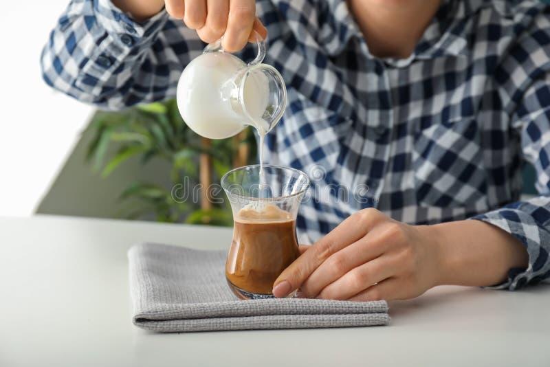 Lait se renversant de femme dans le verre avec le latte aromatique à la table légère photos stock
