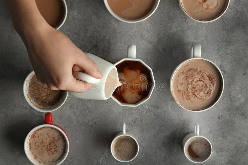 Lait se renversant de femme dans une de beaucoup de tasses avec du café aromatique savoureux sur la table, vue supérieure images stock