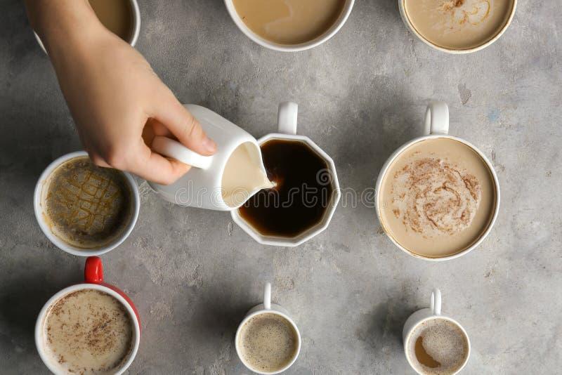Lait se renversant de femme dans une de beaucoup de tasses avec du café aromatique savoureux sur la table, vue supérieure photo libre de droits