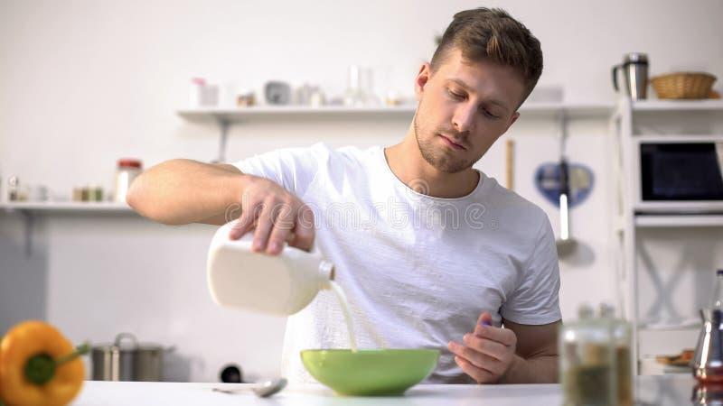 Lait se renversant masculin dans la cuvette avec des flocons d'avoine, nourrir et petit déjeuner sain image libre de droits