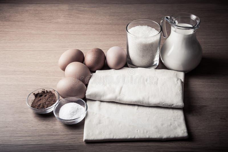 Lait, sucre, cacao, pâte de souffle, oeufs et sel sur un conseil en bois images stock