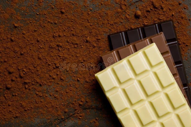 Lajes do branco, do leite e do chocolate escuro sobre se em uma ardósia preta espanada com pó de cacau de cima de Espa?o para o t fotos de stock royalty free