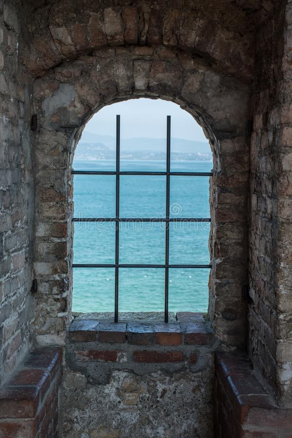 Lake view through the window of a medieval castle. In Italy stock photos