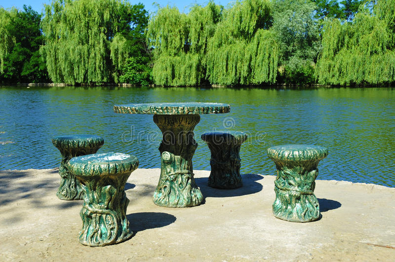 Lake. In a park. Old furniture from bronze stock photos