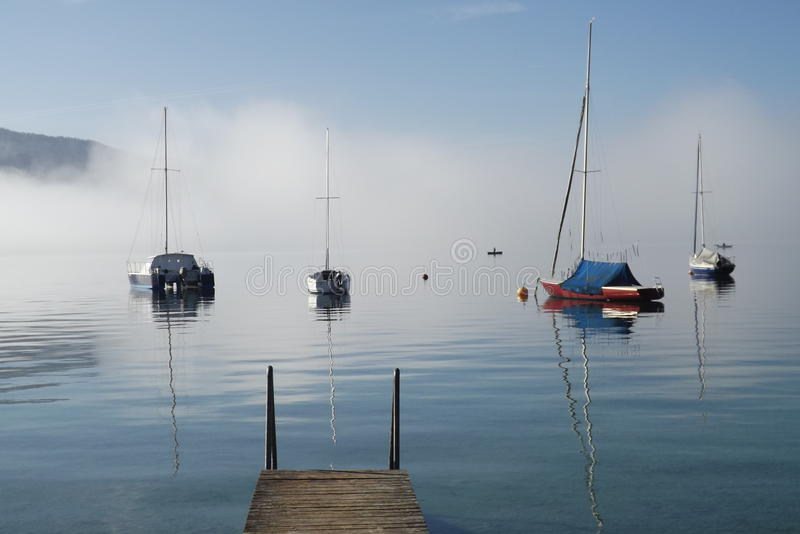 Lake Attersee in Austria, Europe. Small sailing boats in the morning fog stock photos