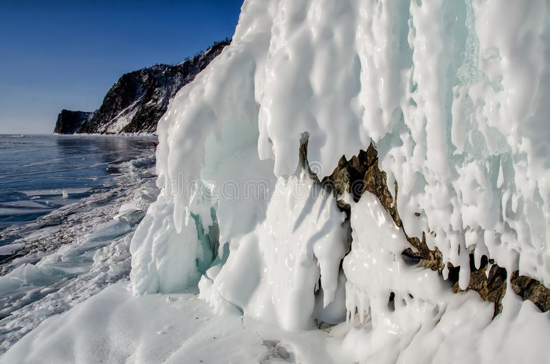 Lake Baikal is covered with ice and snow, strong cold, thick clear blue ice. Icicles hang from the rocks. Lake Baikal is royalty free stock photo