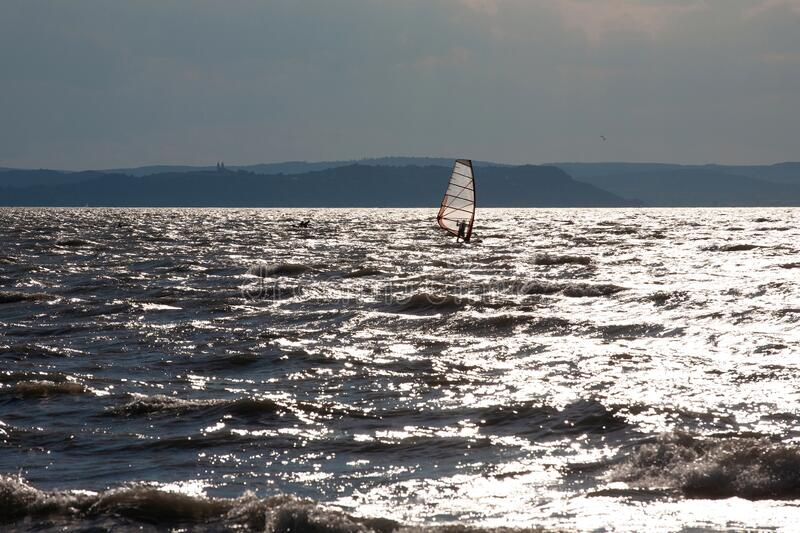 Lake Balaton in backlight with silver waves and a silhouette of a windsurfer stock image