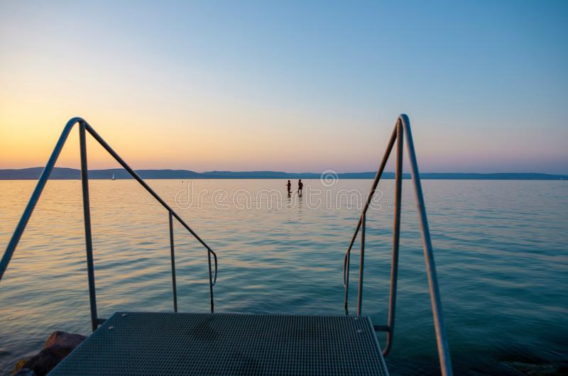 Lake Balaton at sunset with bathers and a stairs to the water. In the foreground stock images