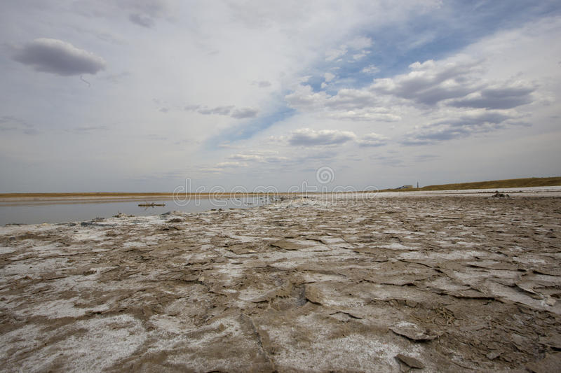Lake Baskunchak. Salt lake Baskunchak, Astrakhan region, traces of the car on the ground covered with salt. On the horizon is visible salt producing plant royalty free stock image