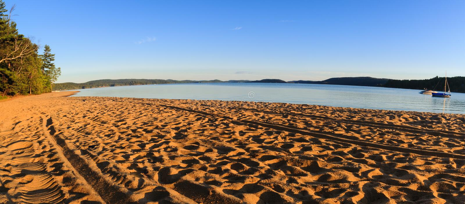 Golden destination place for vacations in summer or autumn season. Touristic beach of golden sand with traces of people at sunset. Lake Simon from Quebec royalty free stock photography
