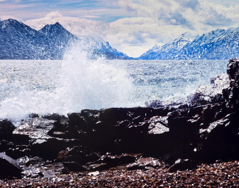 Lake Bennett scenery rock shore surf Yukon Canada. Strong wind and high waves on Lake Bennett rocky shore with distant high mountains on oposite lake side, Yukon royalty free stock photography
