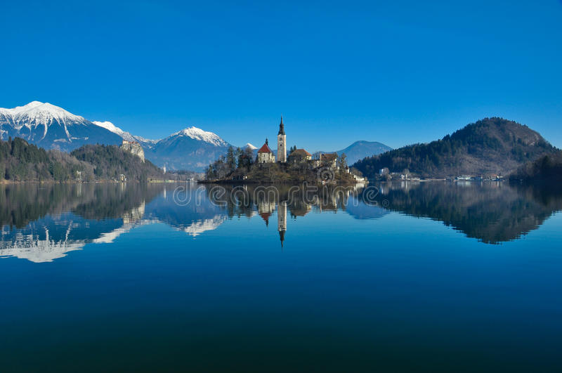 Lake Bled. A shot of a church in the island of the lake bled with nice reflections of mountains in the water royalty free stock photography