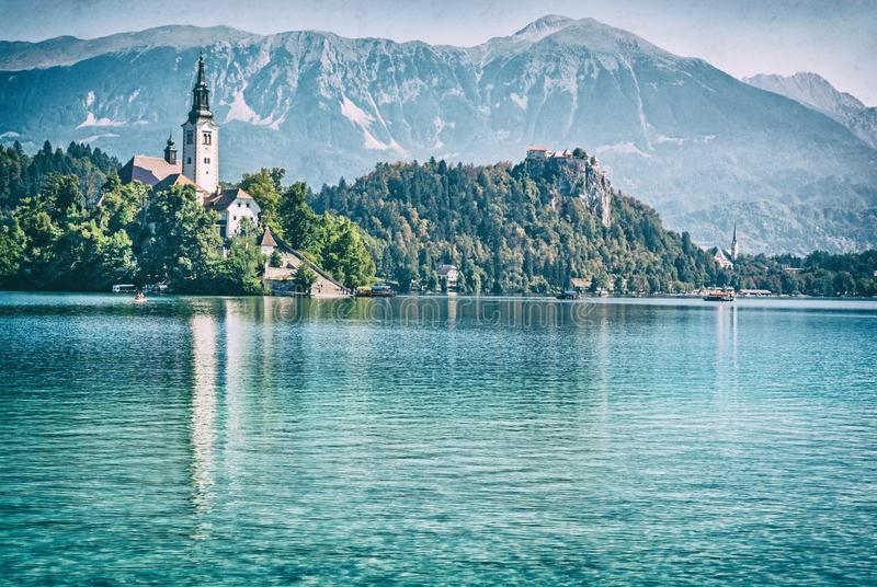 Lake Bled with castle and Assumption of Mary Pilgrimage Church. Slovenia, Europe. Travel destination. Mountains, architecture and reflections in water. Analog stock images