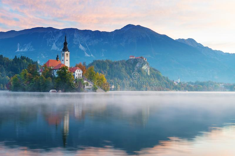 Lake Bled in the morning. Church on island, castle and mountains in background. Beautiful morning view of lake Bled during sunrise in autumn. Old catholic church stock image
