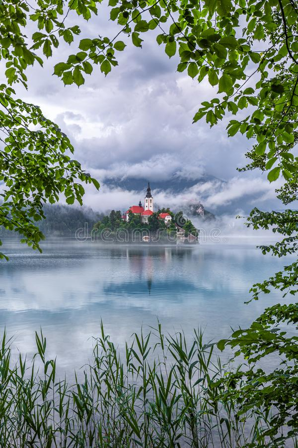 Lake Bled, Slovenia - Beautiful Lake Bled Blejsko Jezero with the Pilgrimage Church of the Assumption of Maria, Bled Castle. And Julian Alps on a misty summer royalty free stock photos