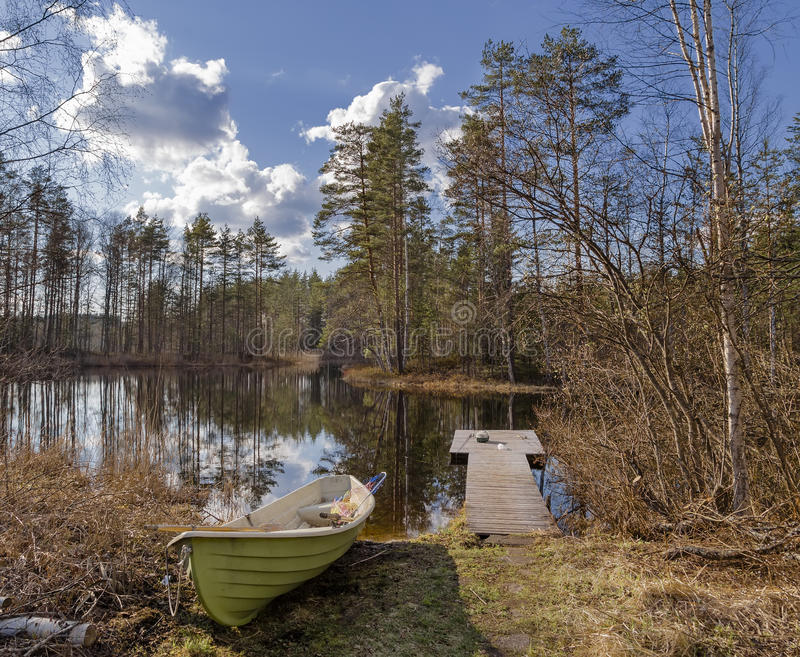 Lake with a boat and facilities for fishing. Scenic lake with a boat and facilities for fishing in the spring sunny day stock photography