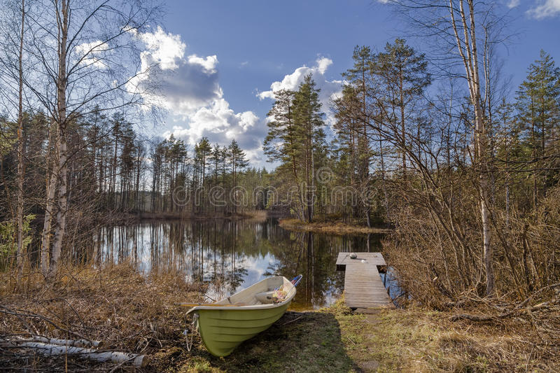 Lake with a boat and facilities for fishing. Scenic lake with a boat and facilities for fishing in the spring sunny day royalty free stock photography