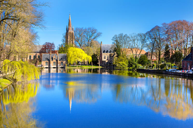 Lake in Bruges, Belgium, church and medieval houses reflection in water. Lake panorama in Bruges, Belgium, church and medieval houses reflection in water, blue stock photo