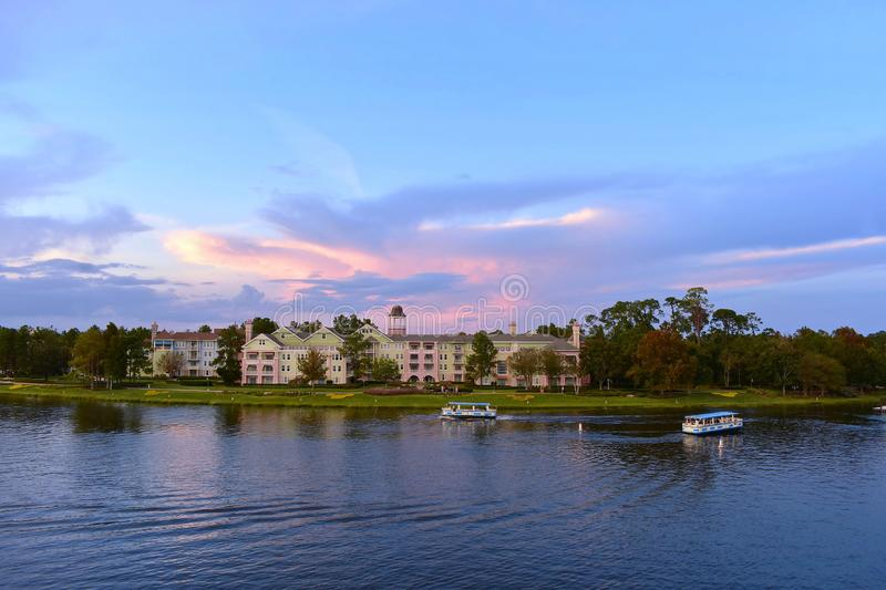 At Lake Buena Vista. Ferry boats and victorian style hotel on colorful sunset background in Lake Buena Vista. Orlando, Florida. November 24, 2018 at Lake Buena royalty free stock image