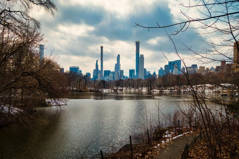 Lake in Central Park with Skyline of Manhattan New York in background. Lake in Central Park with Skyline of Manhattan in background. Dramatic, cloudy sky in New royalty free stock photography