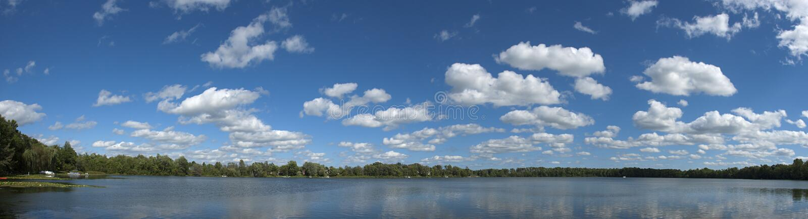 Lake Clouds Sky Water Panoramic, Panorama, Banner. Quiet fishing lake panorama with clouds and sky. Unique panoramic banner image with peaceful and serene water royalty free stock image