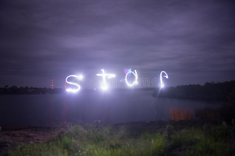 Lake on cloudy night lightpainting of star stock photography