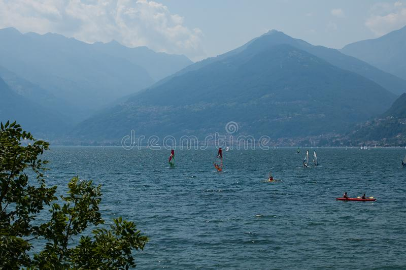 Lake Como, Italy - July 21, 2019: View of mountain lake on a sunny summer day. Windsurfers and a boat passing. District of Como. Lake, Alps, Colico, Italy royalty free stock photography