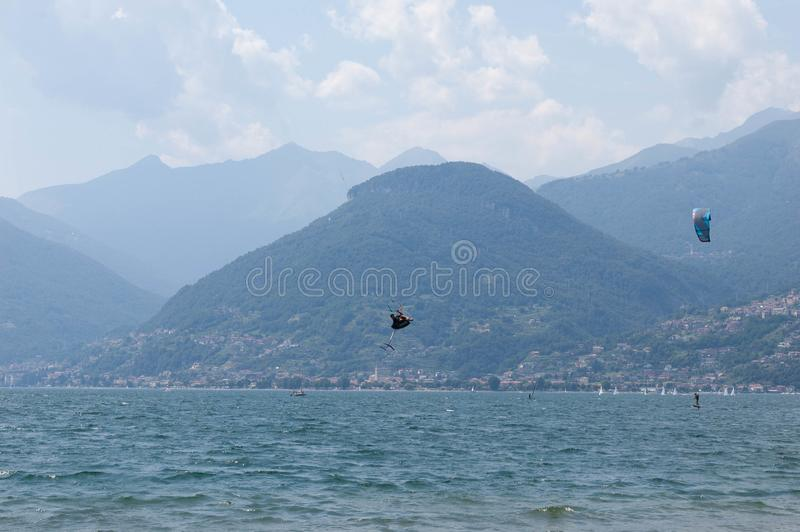 Lake Como, Italy - July 21, 2019. Water sport: kitesurfer is making a trick in the air on a bright sunny summer day near the. Colico, town in Italy. Alp stock photography