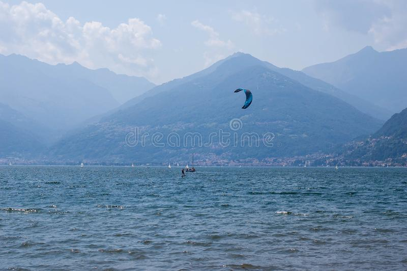 Lake Como, Italy - July 21, 2019. Water sport: kitesurfer surfing the wind on waves on bright sunny summer day near the Colico,. Town in Italy. Alp mountains on stock images