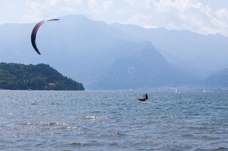 Lake Como, Italy - July 21, 2019. Water sport: kitesurfer surfing the wind on waves on bright sunny summer day near the Colico,. Town in Italy. Pomontory and stock image