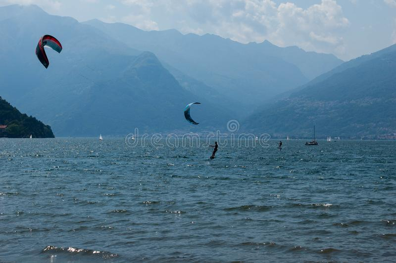 Lake Como, Italy - July 21, 2019. Water sport: kitesurfers surfing the wind on waves on bright sunny summer day near the Colico,. Town in Italy. Pomontory and royalty free stock image