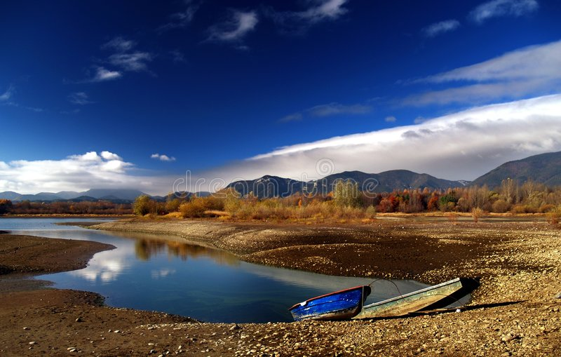 Lake in countryside. Scenic view of picturesque lake in countryside with two rowing boats moored in foreground stock image