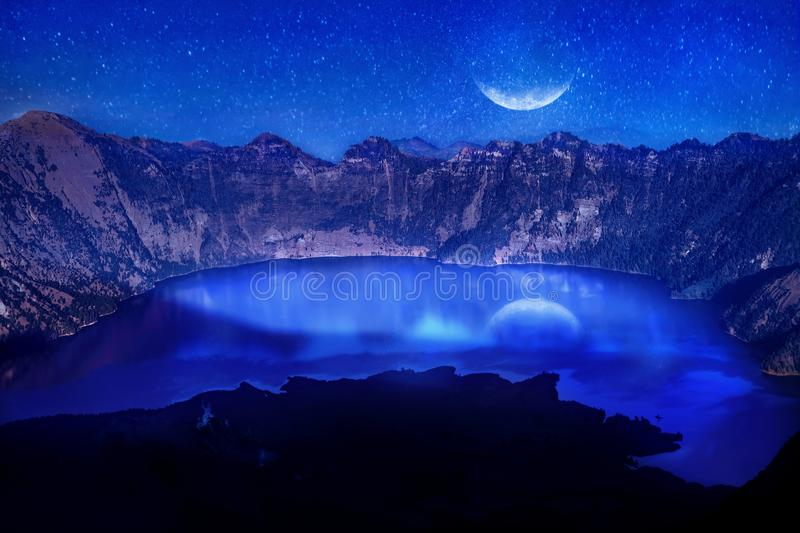 Lake in the crater of a volcano against the background of the starry sky. Reflection of the moonlight on the water. Indonesia. Rin royalty free stock photography