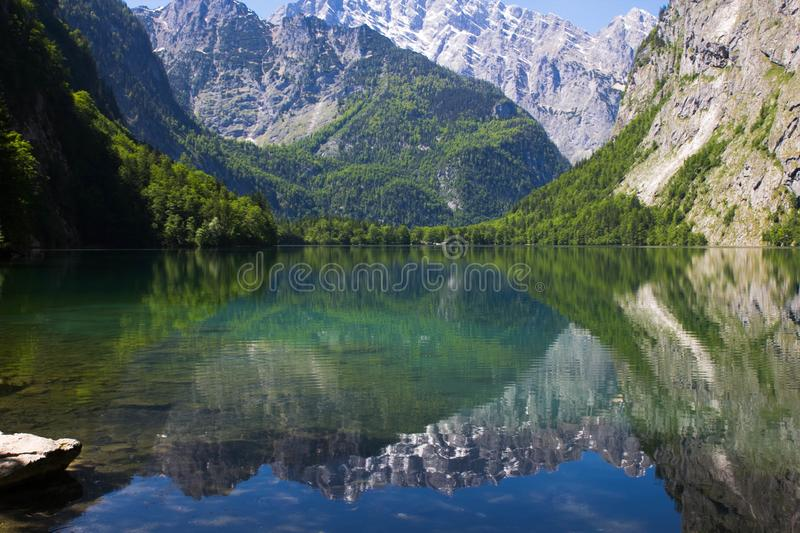 Lake with crystal clear water in the spring mountains. A small lake in the Alps view from one shore. Reflection of mountains in stock image