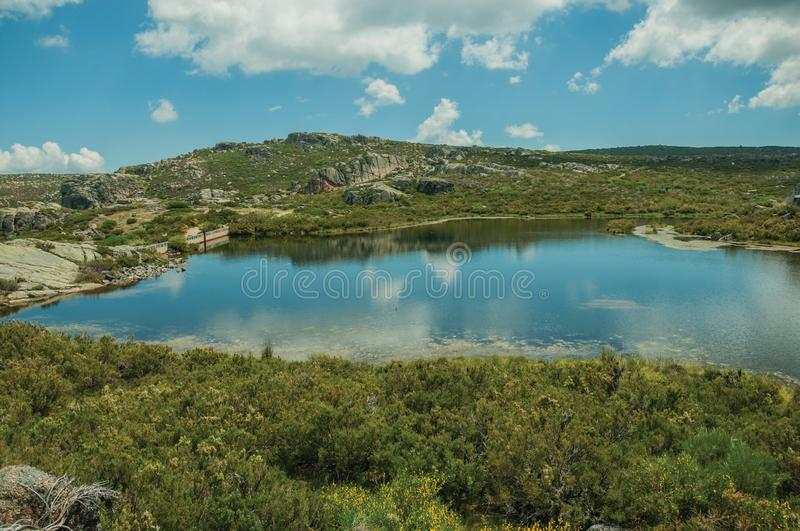Lake from dam in a rocky terrain on highlands. Blue fresh water at the Covao dos Conchos dam lake on the rocky highlands, in a sunny day at the Serra da Estrela stock images