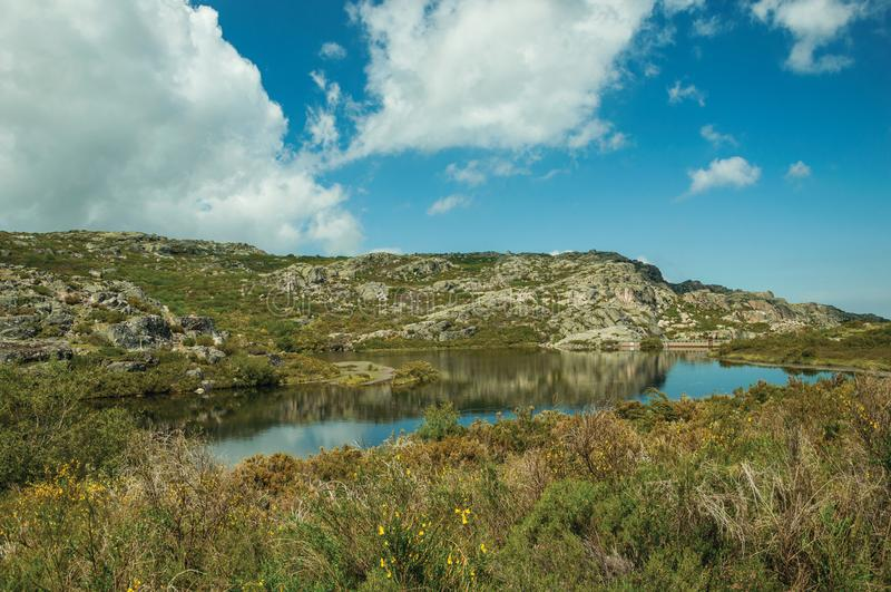Lake from dam in a rocky terrain on highlands. Dam lake at the Covao dos Conchos on rocky terrain and bushes on highlands, in a sunny day at the Serra da Estrela royalty free stock photo