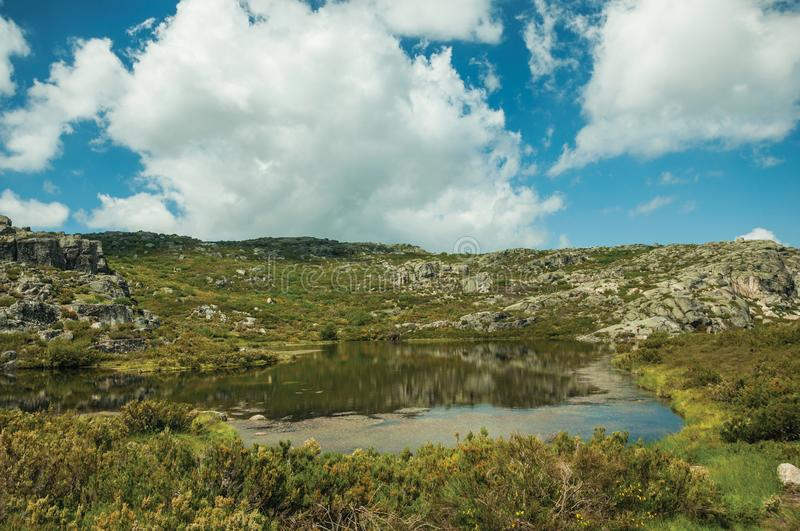 Lake from dam in a rocky terrain on highlands. Dam lake at the Covao dos Conchos on rocky terrain and bushes on highlands, in a sunny day at the Serra da Estrela royalty free stock photography