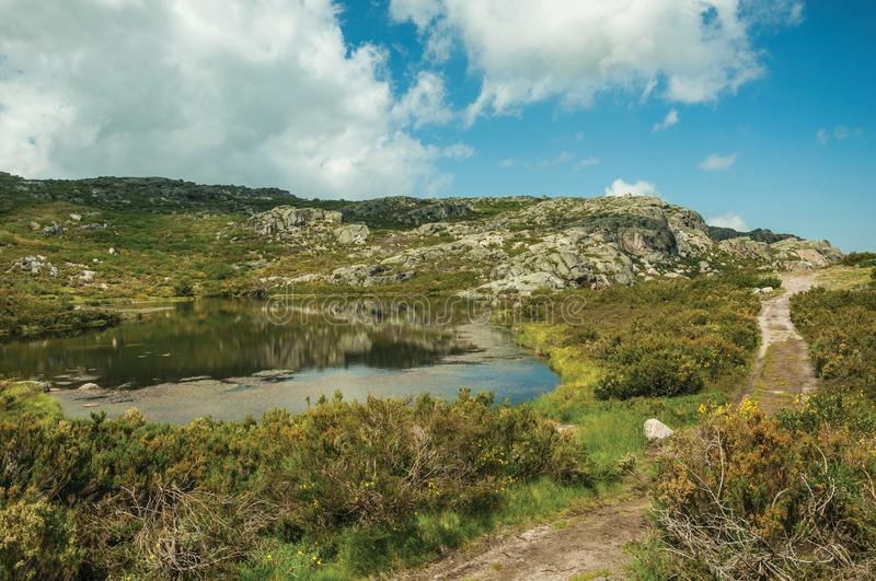 Lake from dam in a rocky terrain on highlands. Dam lake at the Covao dos Conchos among rocky terrain and trails on highlands, in a sunny day at the Serra da royalty free stock photography