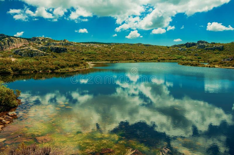 Lake from dam in a rocky terrain on highlands. Crystal clear water at the Covao dos Conchos dam lake with reflected sky at the Serra da Estrela. The highest royalty free stock photos