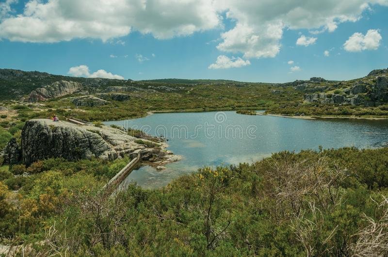 Lake from dam in a rocky terrain on highlands. People resting on a big rock at the Covao dos Conchos dam lake on the highlands, in a sunny day at the Serra da stock photography