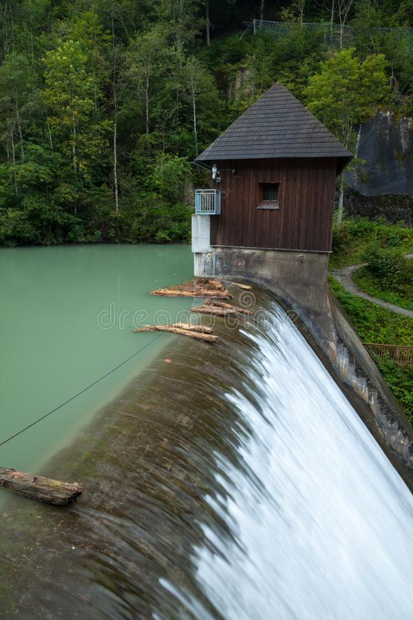 A lake and and dam in the woods in Austria royalty free stock image