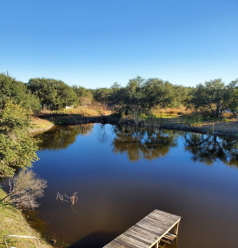 Lake dock trees pond sky royalty free stock photo