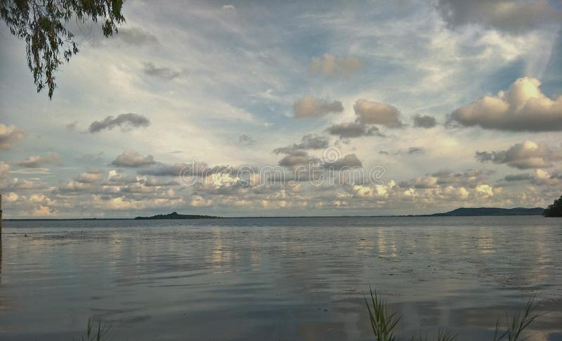Lake in the evening. A lake is an area filled with water, localized in a basin, that is surrounded by land, apart from any river or other outlet that serves to royalty free stock photography